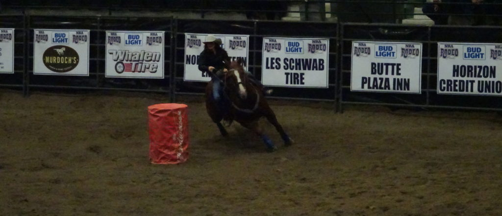 Cowgirl making a turn while participating in barrel racing.